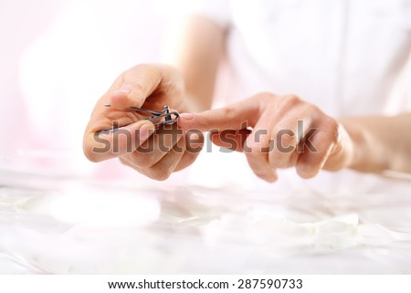 Clipping nails, hand care.The woman cuts the nails, manicure home  - stock photo