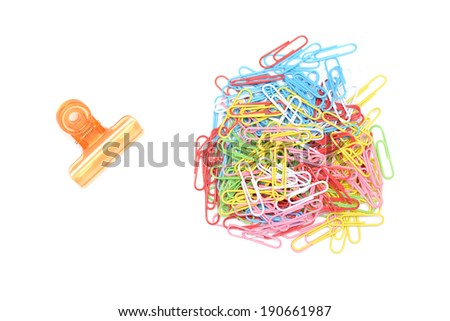 Clips and multi color paper clips arrangedon isolated white back - stock photo
