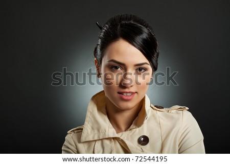 cloaeup portrait of a beautiful woman wearing trench coat - stock photo
