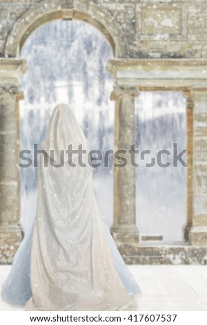 cloaked woman by castle lake - stock photo