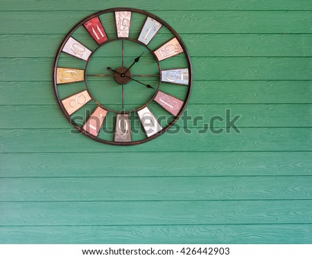 Clock analog green wooden wall background. - stock photo