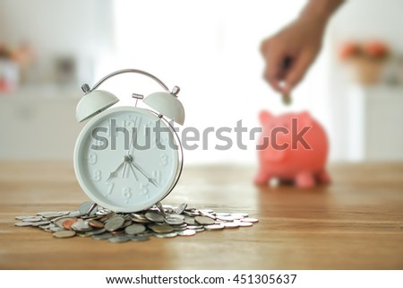 clock and blur background of hand putting add money to piggy bank save coin. time and money concept. - stock photo