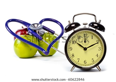 Clock and hearth shaped stethoscope with green and red apples - stock photo