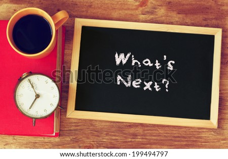 clock, coffee, and blackboad with the phrase whats next? written on it. - stock photo