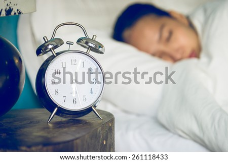Clock in bedroom with woman sleeping - stock photo
