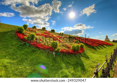 clock made of flowers on a background of a beautiful sky - stock photo