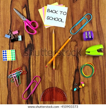 Clock made of school supplies with Back to School notes over a wooden desk background - stock photo