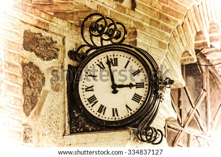 clock on a brick wall in vintage tone effect - stock photo
