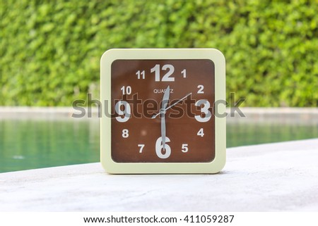 Clock on concrete floor at 12.30 P.M. - stock photo
