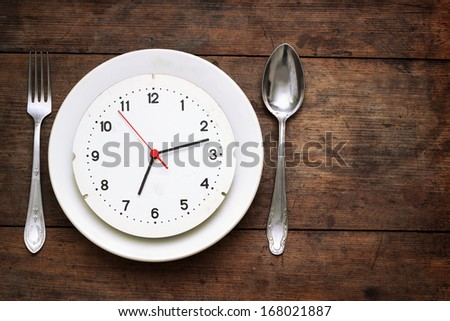 Clock on the plate on wooden background - stock photo