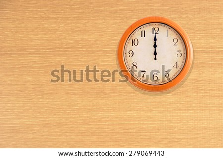 Clock showing 12 o'clock on a wooden wall - stock photo