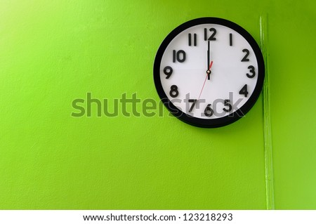 Clock showing 12 o'clock pm on a green wall - stock photo