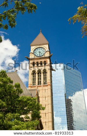 Clock tower of Toronto's Old City Hall against modern building. - stock photo