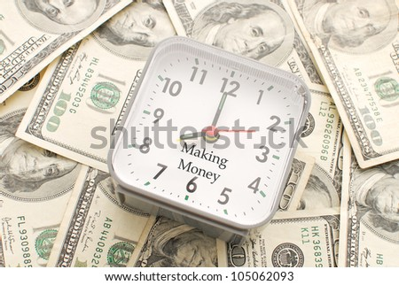 Clock with Making Money Caption on a Pile of Hundred Dollar Bills - stock photo