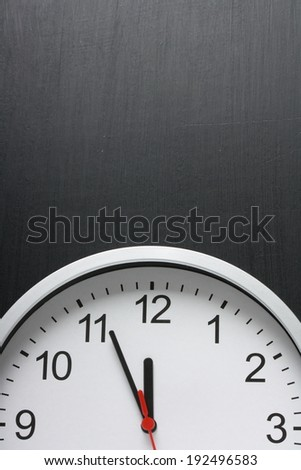 Clock with the time approaching midnight and copy space on a used blackboard - stock photo