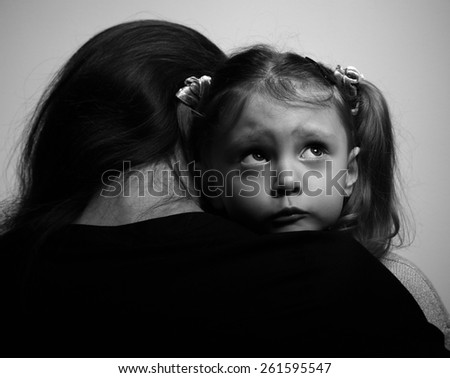 Close between loving supporting mother and sad daughter looking with hope on dark background. Black and white portrait - stock photo