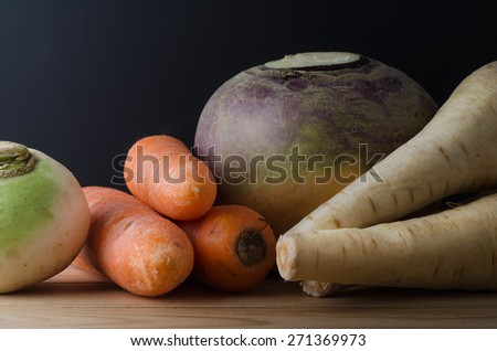 Close cropped shot of still life arrangement.  Raw, unwashed root vegetables on a wood plank table with a black chalkboard background.  Includes turnip, carrots, swede and parsnips. - stock photo