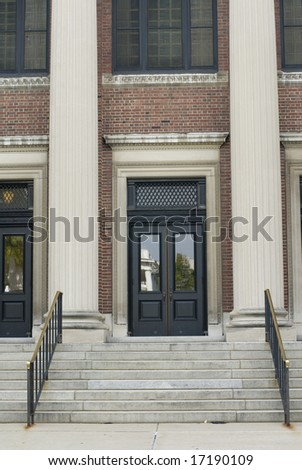 Close detail of the front doors of a columned building. - stock photo