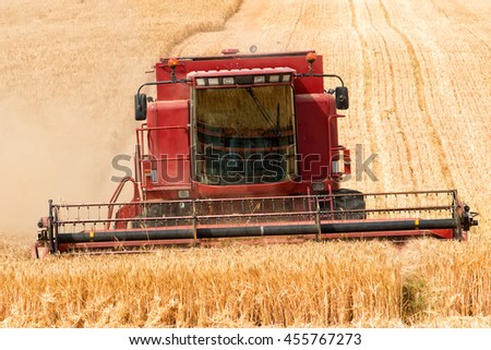close front view of combine harvester in action - stock photo