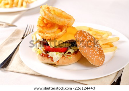 Close Gourmet Mouth Watering Burger with Lettuce, Cheese, Tomatoes and Onion Rings on White Plate with French Fries on the Side. Served at the Restaurant. - stock photo