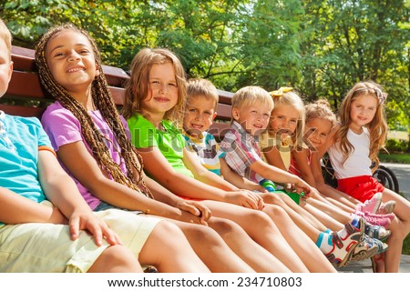 Close group portrait of happy little diverse looking boys and girls sitting on the bench in the nice park  - stock photo
