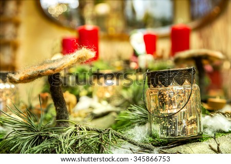 Close look to an advent wreath with handmade felt mushroom and candle illuminated glass potty in the foreground - stock photo