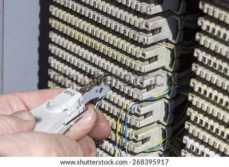 Close of hands punching down circuit panel used for phones. Using a punch down tool punch the wires down into the blades built into the communication circuit for analog phones. - stock photo