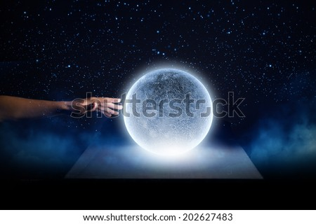 Close of man hands touching moon planet - stock photo