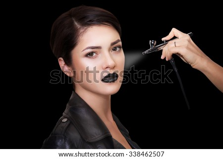 close portrait of a beautiful girl with make-up . Make up with airbrush. Isolated on black background. Copy space. - stock photo