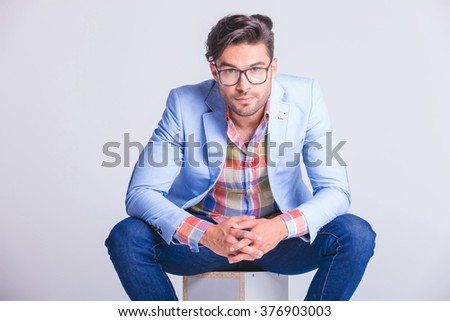 close portrait of attractive businessman seated with legs spread open, touching hands, while wearing glasses and looking at the camera in studio background - stock photo
