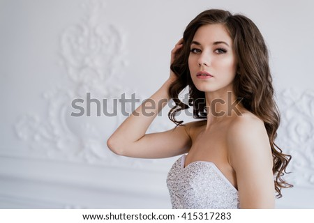 Close portrait of beautiful smiling bride woman with long curly hair posing in wedding dress at interior and smiling. Beauty indoor portrait. - stock photo