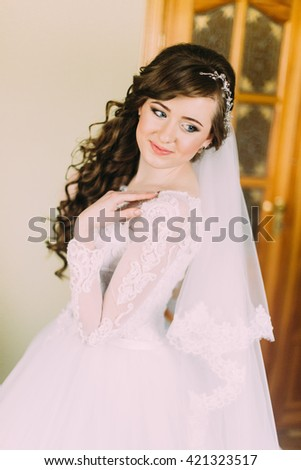 Close portrait of beautiful smiling bride woman with long curly hair posing in wedding dress at interior and smiling.  - stock photo