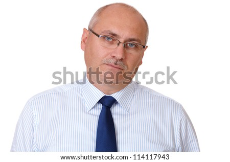 Close portrait of bored senior businessman in blue shirt looking through glasses, isolated on white - stock photo