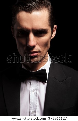close portrait of classy man in tuxedo with bowtie posing in dark studio background looking at the camera - stock photo