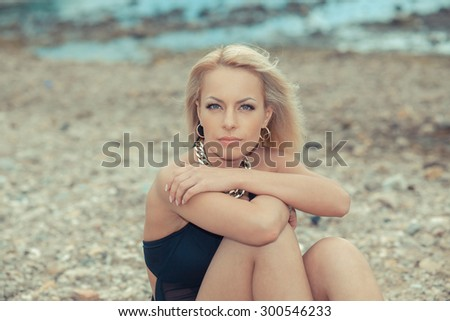 Close portrait of fashionable blond girl in a swimsuit. Pretty young sexy tanned woman in bikini posing On the stone seashore  - stock photo