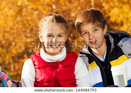 Close portrait of happy and smiling couple children, boy and girl sitting on the bench in autumn park - stock photo