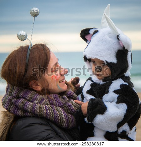 Close portrait of mother and daughter in her carnival costume at the beach - stock photo