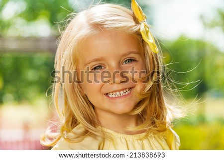 Close portrait of smiling happy blond little girl  - stock photo