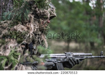 Close portrait of special forces soldier wearing ghillie camouflage, running with machine gun. - stock photo