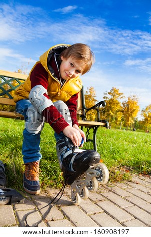 Close portrait of 10 years old boy in casual autumn clothes putting on roller skates sitting on the bench in the park - stock photo