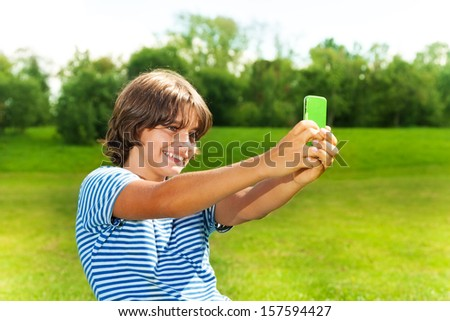 Close portrait of 14 years old boy taking a picture of himself with camera on the cell phone in the park on sunny summer day - stock photo
