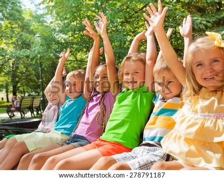 Close portraits of large group of children sitting on the bench in the park with lifted hands and happy cheerful expression lifting hands - stock photo
