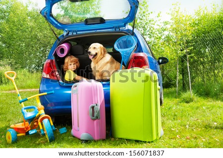 Close shoot of a car with retriever dog and three years old boy waiting in the trunk with bags for trip, trickle, ball, scoop-net - stock photo