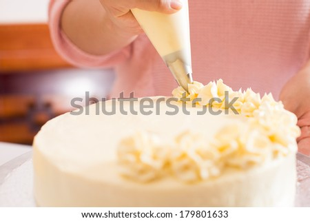 Close shot of a human hand frosting a cake with whipped cream on the foreground  - stock photo