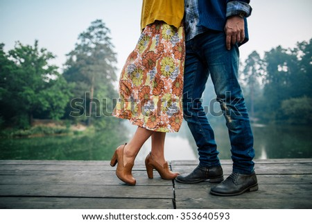 close shot of couple embracing at the bridge across the forest lake - stock photo