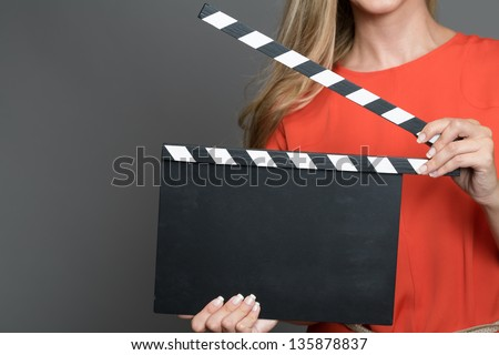 Close up a blond woman with her face not shown holding a movie clapperboard. - stock photo