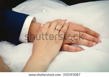 close-up a bride and groom covers of each other's hands with rings - stock photo
