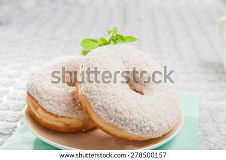 Close up a pair of coconut  donuts with vanilla cream on a white plate decorated with mint  on kitchen table - stock photo
