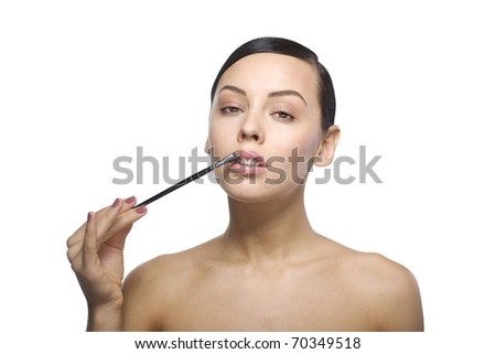 Close up a young beautiful brunette girl with brash near her lips isolated - stock photo