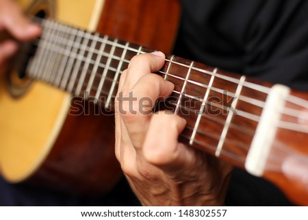 close up acoustic guitar in musician hands, small depth of field - stock photo